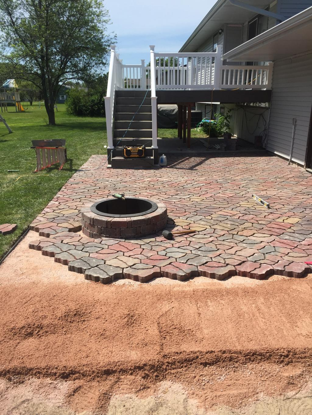 paved patio with deck and fire pit
